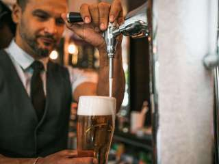 Barman hand at beer tap pouring a draught lager beer serving in a pub.